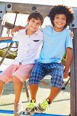Portrait Of Two Boys On Playground Climbing Frame