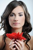Close-up Portrait Of Beautiful Woman With Fresh Purity Skin Of Face And Red Flower In Hand