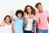 Family Standing Outdoors Against White Wall And Waving