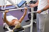 Male trainer with clipboard besides young woman lifting barbell in the gym
