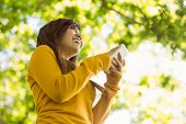 Low angle view of beautiful young woman text messaging in the park