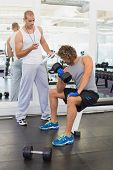Male trainer assisting young man with dumbbell in the gym