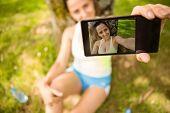 Smiling fit brunette taking a selfie in the park