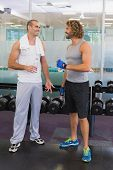 Smiling male trainer talking to fit young man at the gym