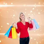 Happy blonde holding shopping bags against bright star pattern on cream