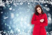 Pretty brunette in red coat posing against blue abstract light spot design