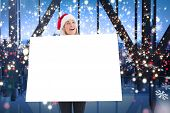 Festive blonde showing poster against glittering lights in room