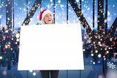 Festive blonde showing poster against glittering lights in room
