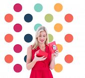 Stylish blonde in red dress opening gift box against colorful polka dot pattern