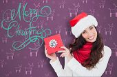 Joyful brunette presenting christmas gift against purple reindeer pattern