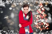 Happy brunette in winter clothes smiling at camera against shimmering christmas tree of lights