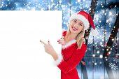 Festive blonde showing white card against glittering lights in room