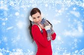 Pretty brunette in winter wear smiling at camera against white snowflake design on blue