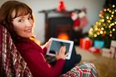 Beauty redhead using tablet at christmas at home in the living room