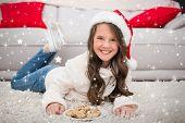 Festive little girl eating cookies against twinkling stars