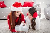 Festive mother and daughter opening a christmas gift against snow
