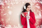 Woman in winter clothes holding a mug against white snowflake design on red
