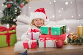 Cute little girl surrounded by christmas gifts against snow