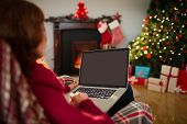 Rear view of redhead using laptop at christmas at home in the living room