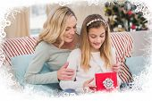 Daughter opening christmas gift with mother against frost frame