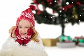 Festive little girl in hat and scarf against snow