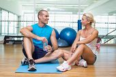 Portrait of a fit young couple sitting on floor at fitness club