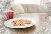 Cookies and mug on coffee table at christmas against frost