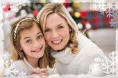 Festive mother and daughter beside christmas tree against christmas themed frame