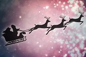 Silhouette of santa claus and reindeer against light design shimmering on red