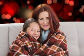 Mother and daughter under blanket against red glowing dots on black