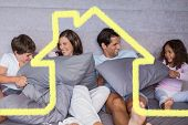 Family having fun together on bed against house outline