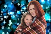 Mother and daughter under blanket against blue glowing dots design pattern