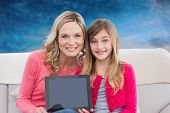 Mother and daughter with tablet against blurred winter scene