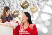 Mother and daughter with gift against christmas decorations hanging from branch