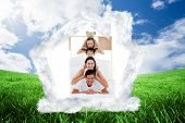 Young Family playing on bed together against green field under blue sky