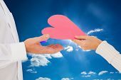 Woman handing man a paper heart against cloudy sky with sunshine