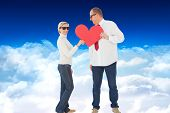 Older affectionate couple holding red heart shape against bright blue sky over clouds