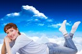 Woman lying on the floor against bright blue sky with clouds