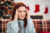 Woman getting a head ache at christmas against snowflakes