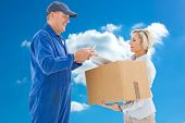 Happy delivery man with customer against cloudy sky