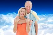 Happy older couple holding paint roller against bright blue sky over clouds