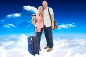Smiling older couple going on their holidays against bright blue sky with clouds