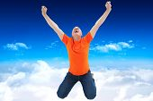Mature man in orange tshirt cheering while kneeling against bright blue sky over clouds