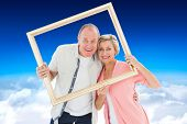 Older couple smiling at camera through picture frame against blue sky over clouds