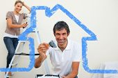 Smiling couple painting a wall against house outline