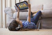 Little girl using digital tablet in the living room against golden 2015