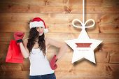 Beauty brunette in boxing gloves with shopping bag against christmas decorations over wood