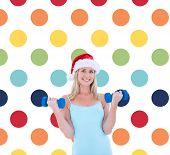 Festive fit blonde holding dumbbells against colorful polka dot pattern