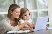 stock photo of self-employment  - Little girl looking at laptop computer with her mom - JPG