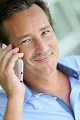 Portrait of 40-year-old man talking on cellphone